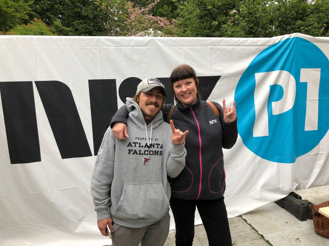 Hilde Zahl and Billy Ray Malone pose in front of the NRK P1 sign outside of the press tent at Bergenfest in Bergen, Norway. Photo by Tom Grant