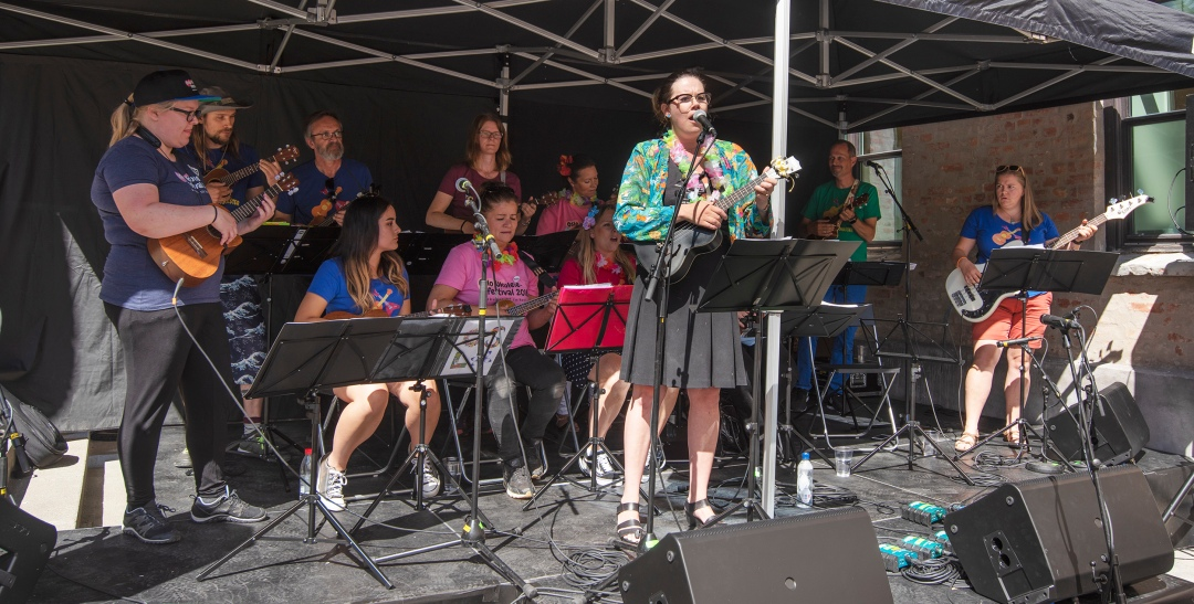 A band playing with ukuleles on stage.
